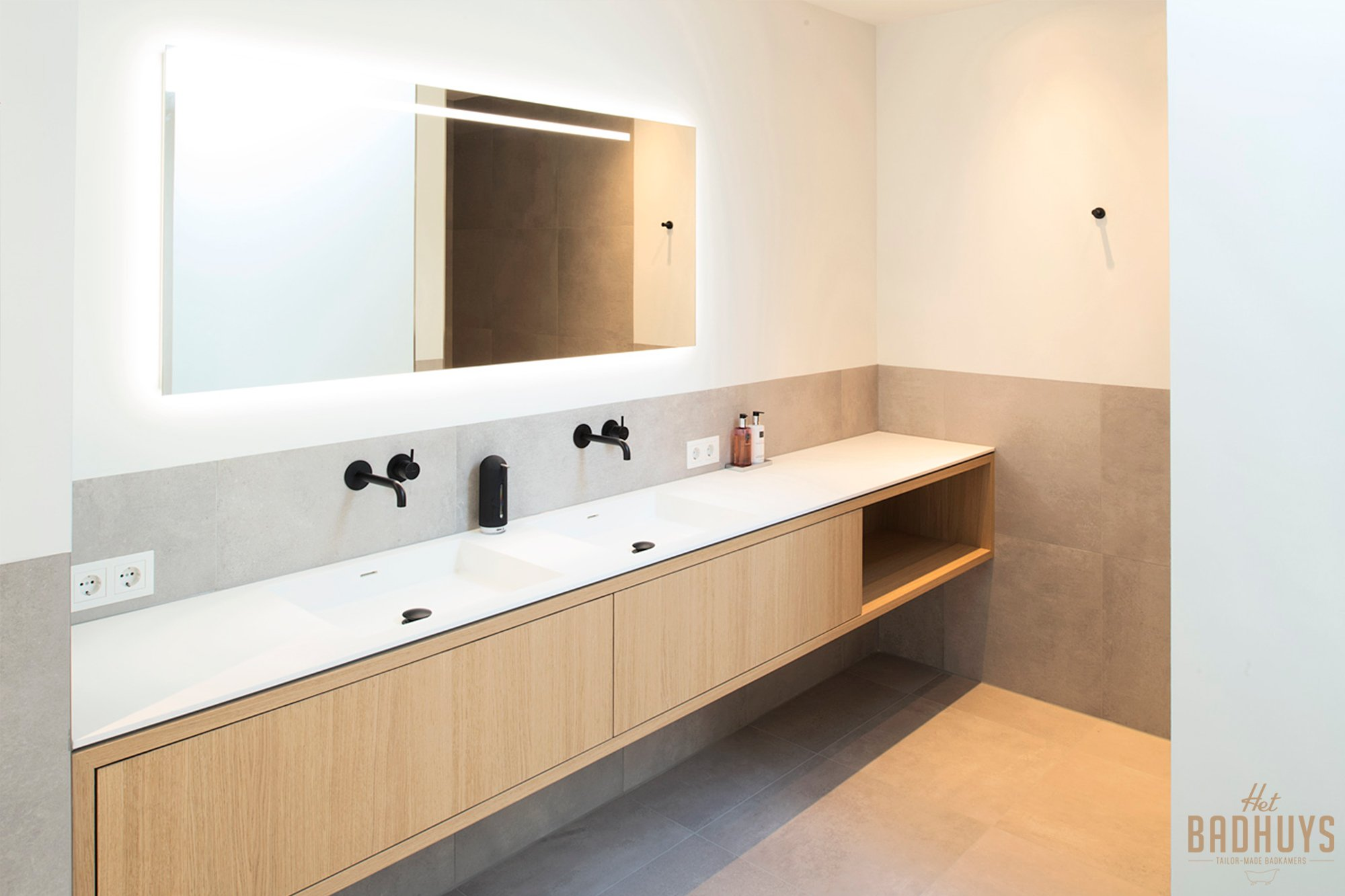 Badkamermeubel op maat in licht eiken met inbouwwastafel, dubbele zwarte kranen en doorlopende spiegel met ingebouwde ledlijn.